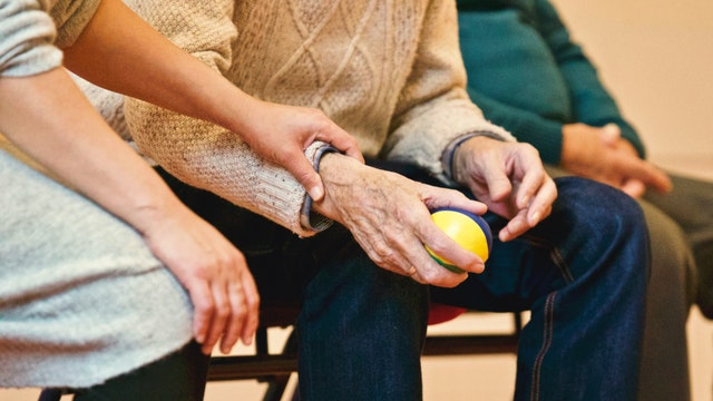 Elderly person with arthritis holding a multi-colored ball may be able to benefit from a specialty medicine compounding pharmacy